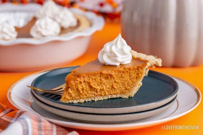 a slice of pumpkin pie on a dark blue plate