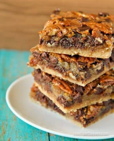 Four stacked pecan pie bars on a white plate
