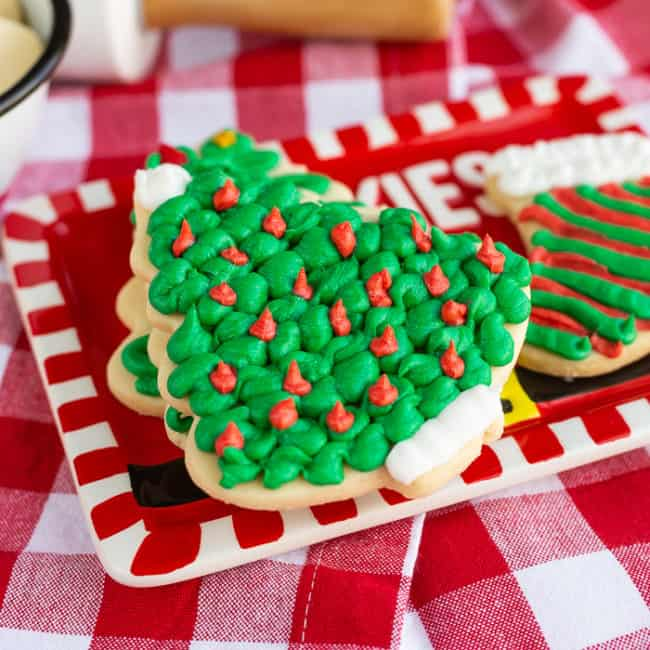 A Christmas tree shaped sugar cookie covered in green frosting on a red plate