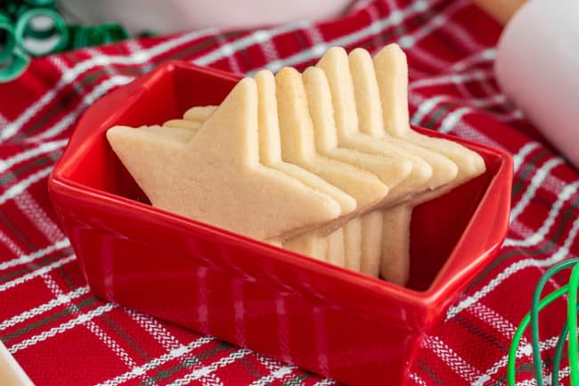Several star shaped sugar cookies in a red container