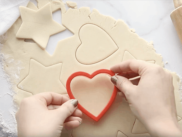 Shapes being cut out of sugar cookie dough