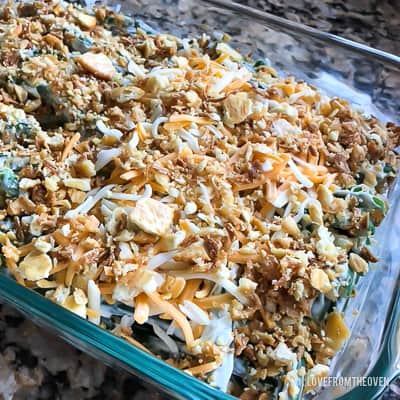 Raw ingredients for green bean casserole in a glass baking pan