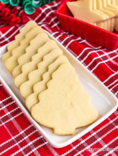 Christmas tree shaped cookies on a white plate with a red napkin