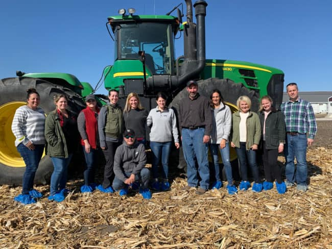 A group of people standing in front of a tractor posing for the camera