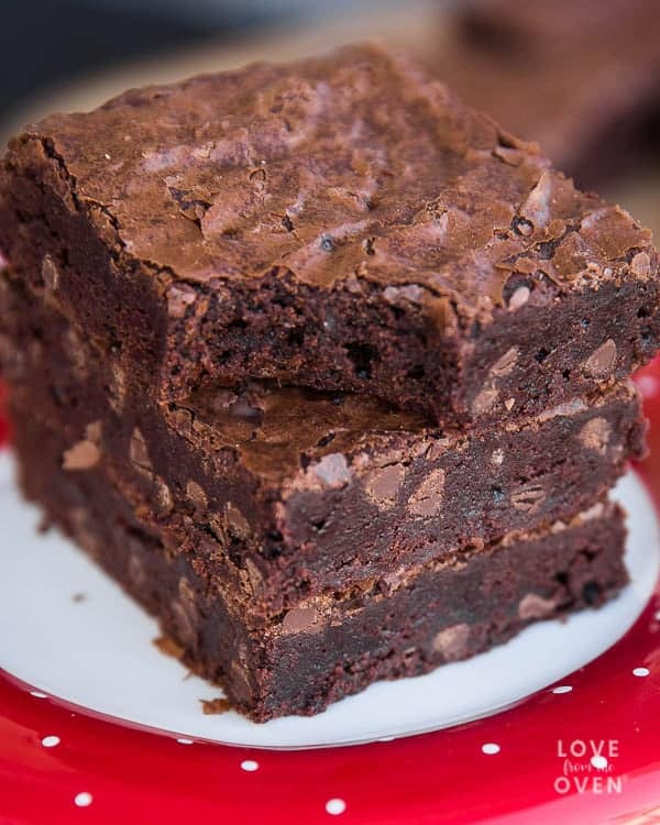 Three stacked brownies on a white and red plate