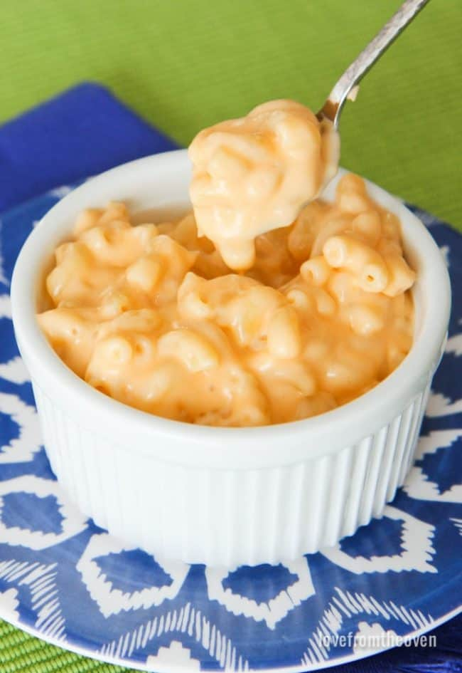 Mac and cheese in a white bowl on a blue plate with a spoonful taken out