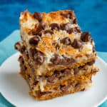 Three stacked magic cookie bars on a white plate