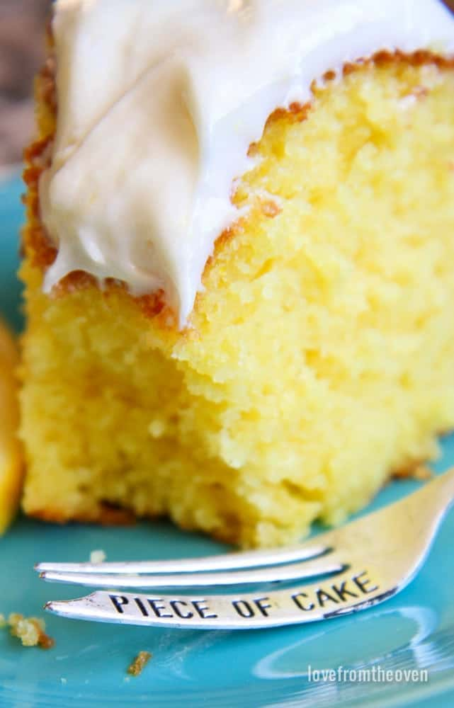 Close up of lemon bundt cake on blue plate with a silver fork