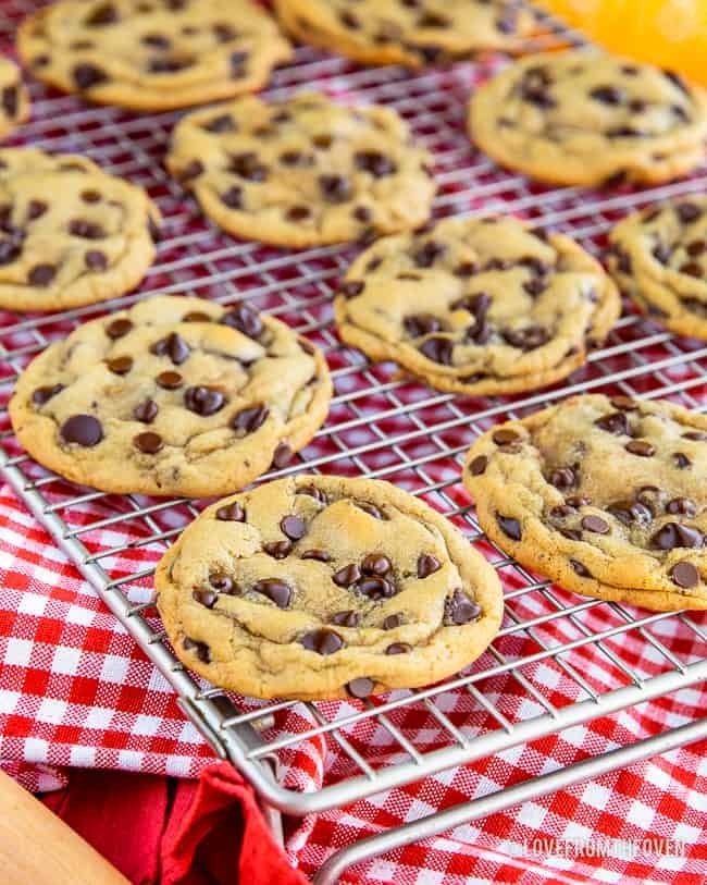 Several Nestle Toll House chocolate chip cookies on wire rack with red and white napkin