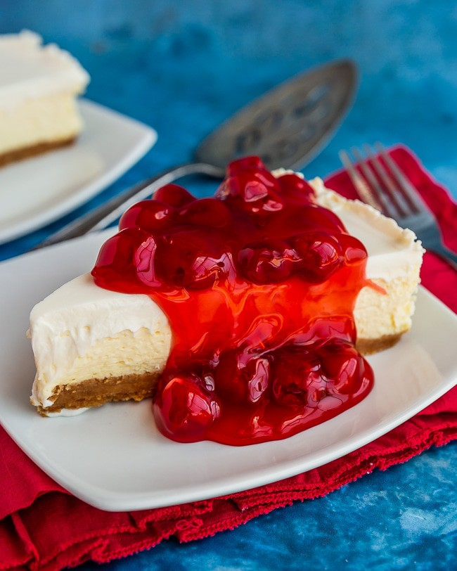 Slice of creamy cheesecake topped with cherries on white plate and red napkin