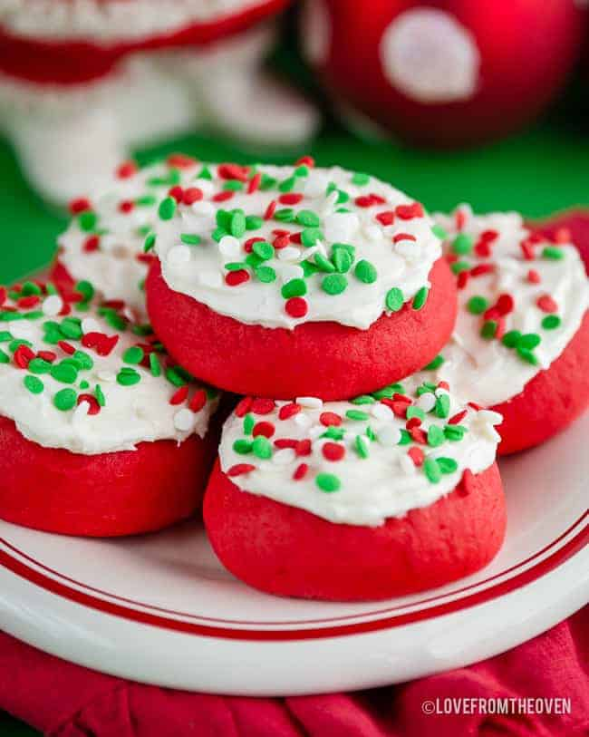 Several lofthouse style cookies with sprinkles on a red and white plate