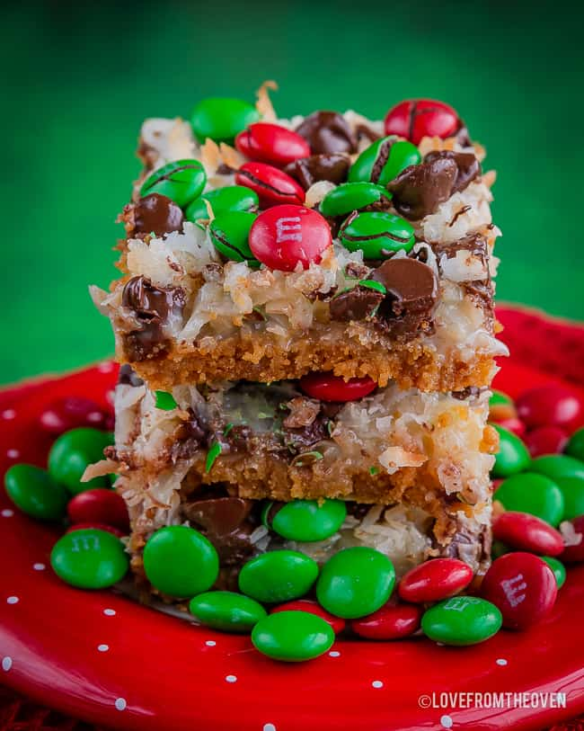 Three stacked magic cookie bars on a red plate