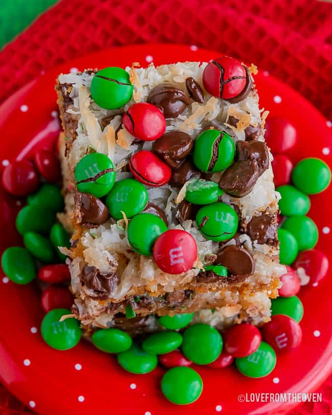 Close up of 7 layer bars covered in M&Ms on a red plate