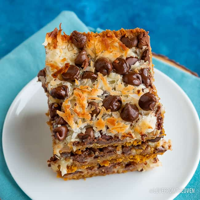 Stack of magic cookie bars made of graham cracker crumbs, sweetened condensed milk, coconut and chocolate chips, stacked on a white plate with a blue background