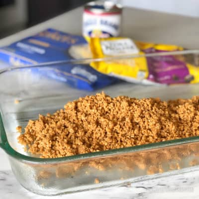 Crushed graham crackers in a glass baking pan