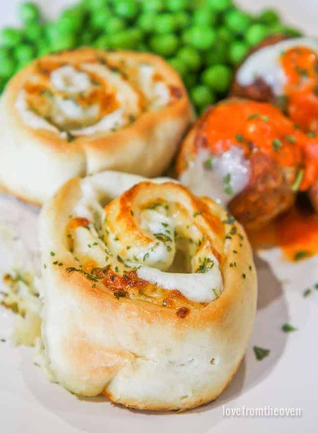 Several cheesy garlic rolls on a plate with meatballs and peas