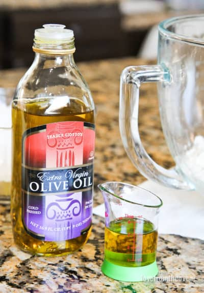 A bottle and measuring cup full of olive oil