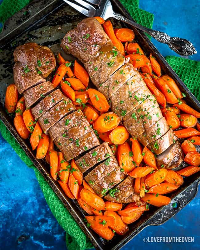 Pork tenderloin on a tray surrounded by seasoned carrots