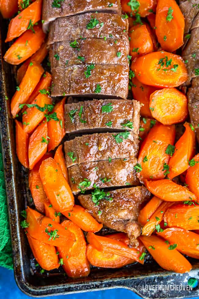 Close up of pork tenderloin surrounded by carrots