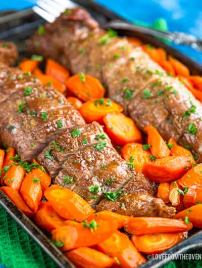 Pork tenderloin on a baking sheet surrounded by carrots
