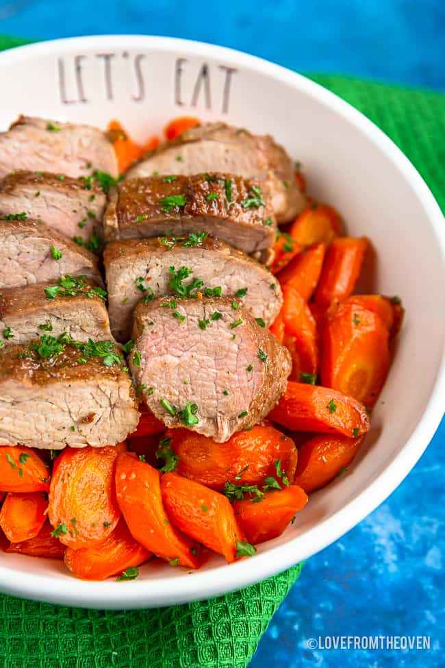 A bowl with brown sugar pork tenderloin on top of carrots sitting on a green napkin with a blue background