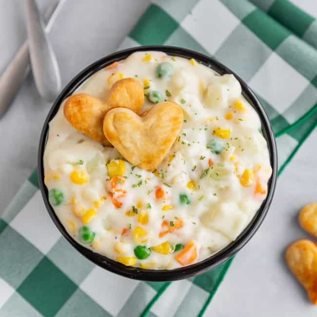 Bowl of pot pie soup on white and green napkin