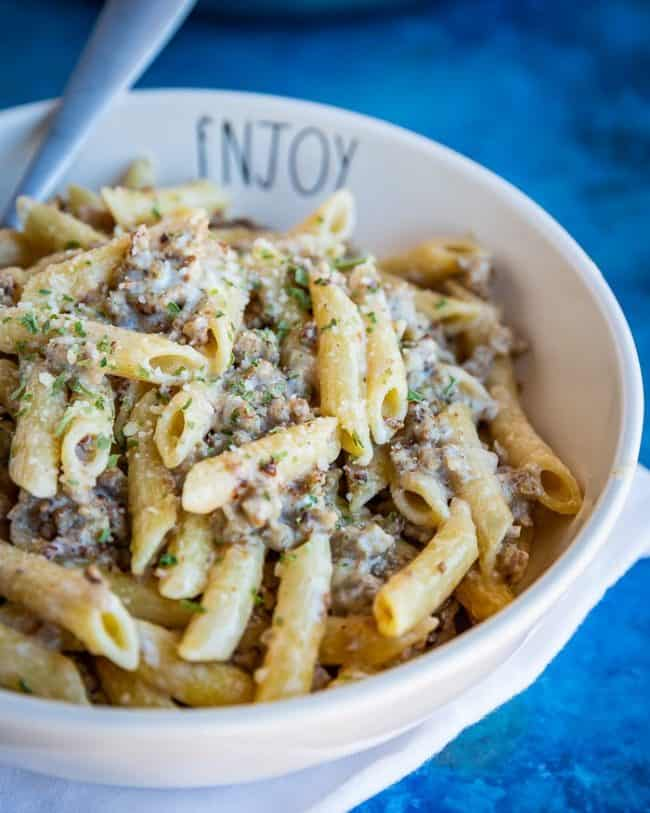 Close up of sausage pasta in a white bowl