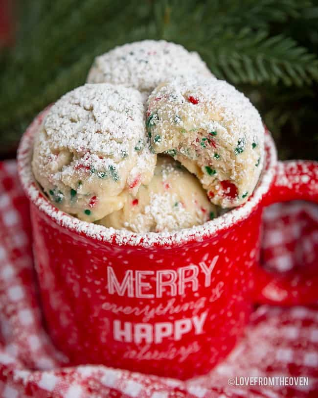 Red mug full of snowball cookies topped with powdered sugar