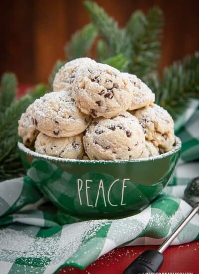 green bowl of chocolate chip snowball cookies with powdered sugar sprinkled on top