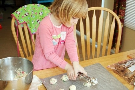 Little girl scooping out cookie dough onto a baking sheet