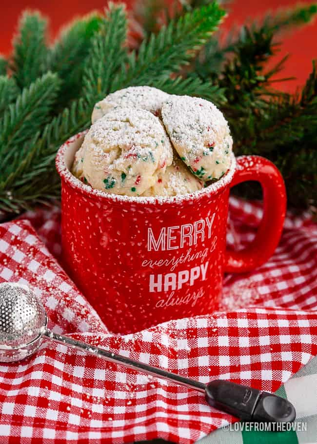 Several snowball cookies in a red mug on a red and white napkin