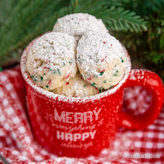 Red mug filled with snowball cookies