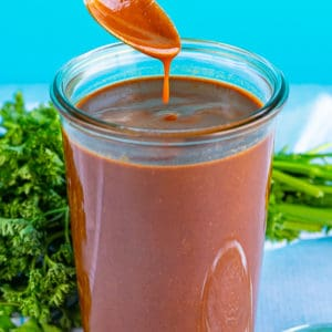 Jar of Easy Red Enchilada Sauce with a spoon dipping into sauce