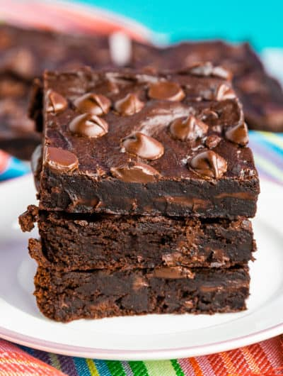 A stack of three black bean brownies, on a white plate with a colorful napkin and a blue background
