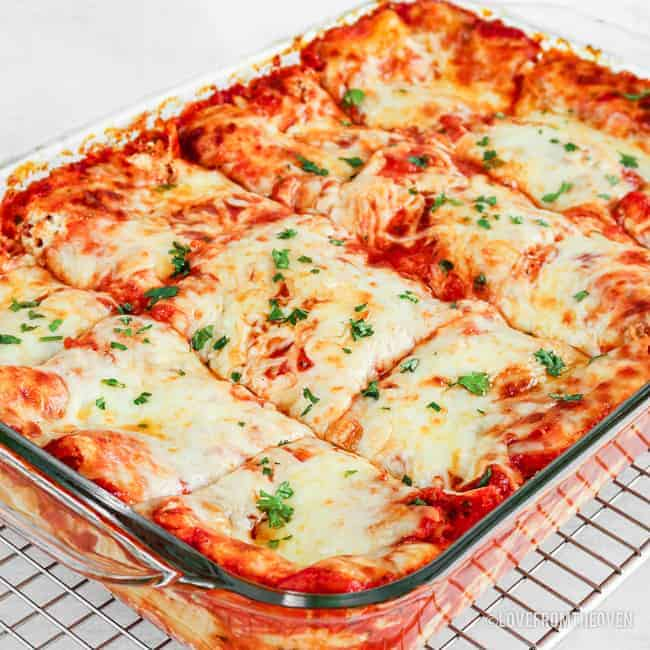 Cheese lasagna cut into square servings in glass baking pan
