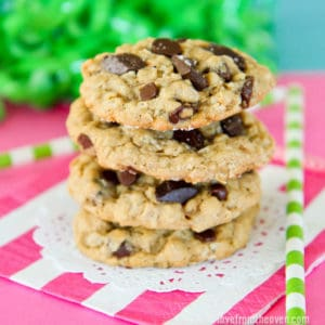 A stack of oatmeal chocolate chip cookies with a pink and white napkin and a blue and green background