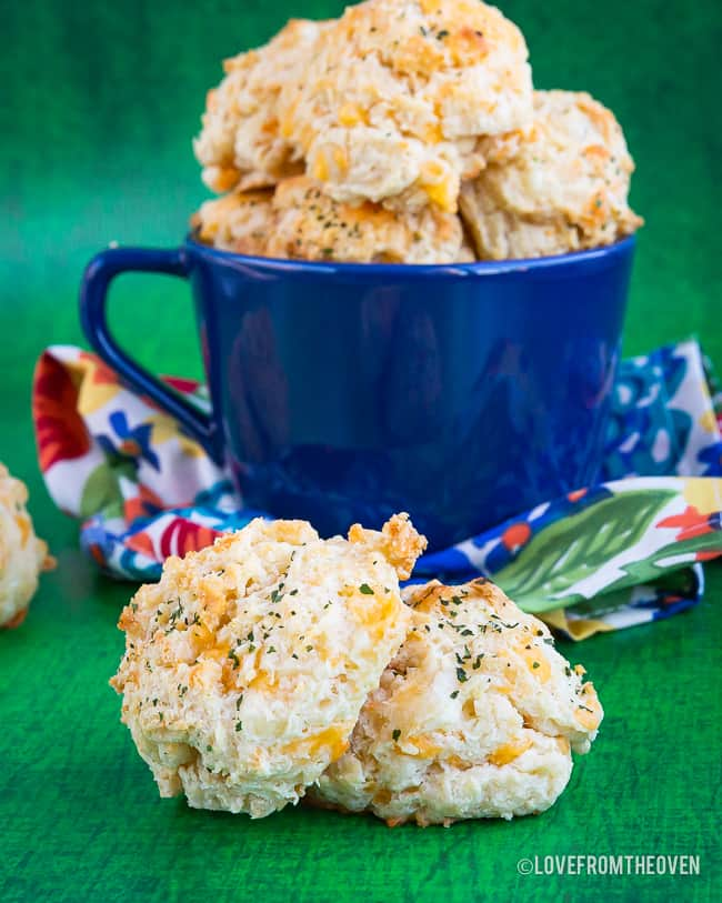 Cheddar bay biscuits in a cup and on a table