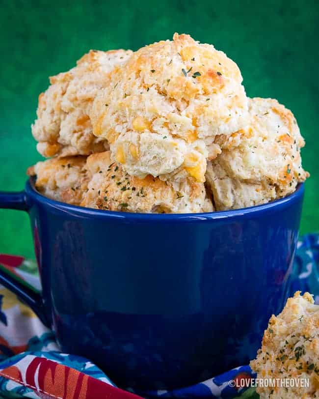 A blue bowl full of cheddar bay biscuits in front of a green backgroud