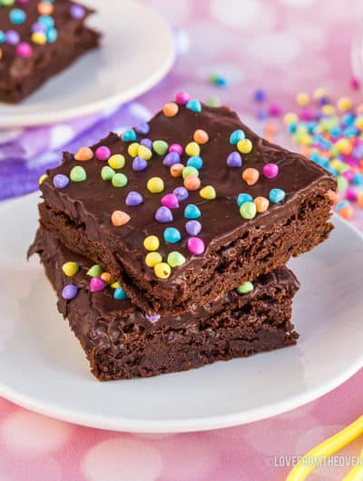 Two brownies with rainbow sprinkles on a plate