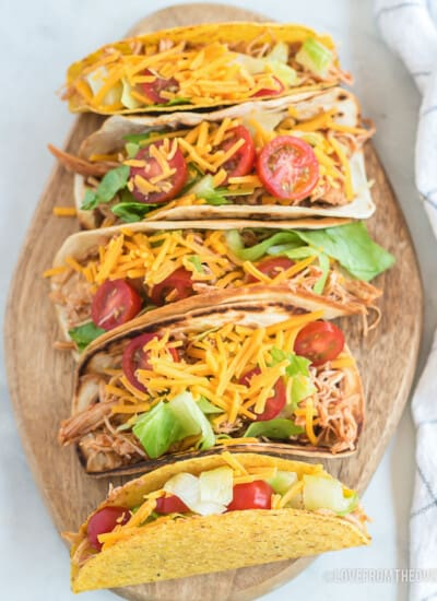 Plate full of chicken tacos on a white background