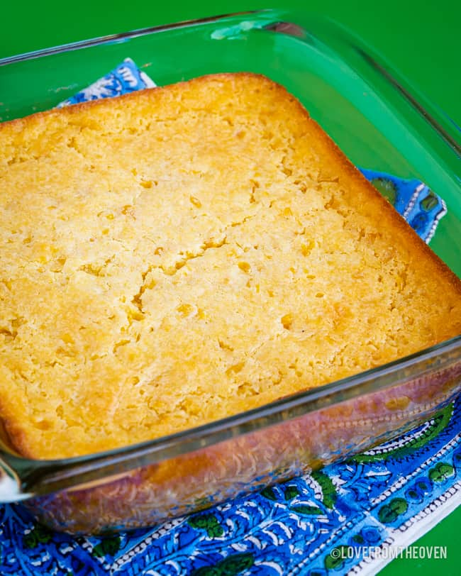 A square pan of corn pudding casserole on a green backround
