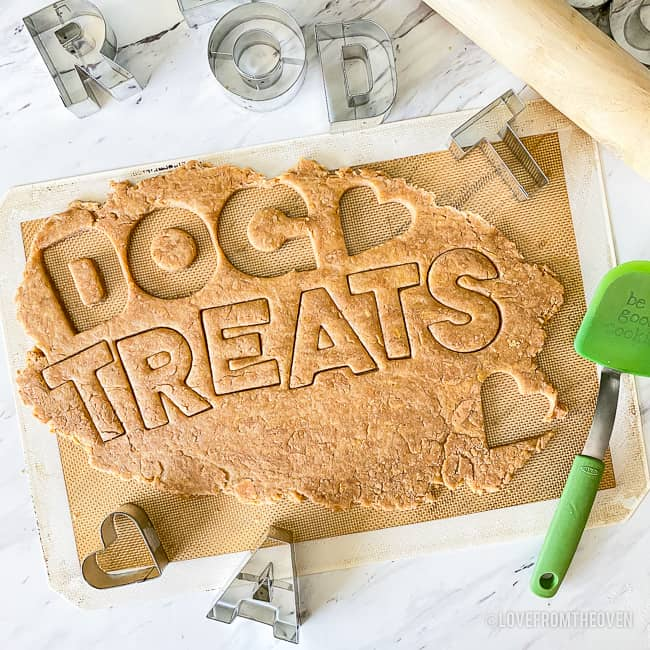 Dough for peanut butter dog treats, rolled out, with cookie cutters cutting out the words dog treats