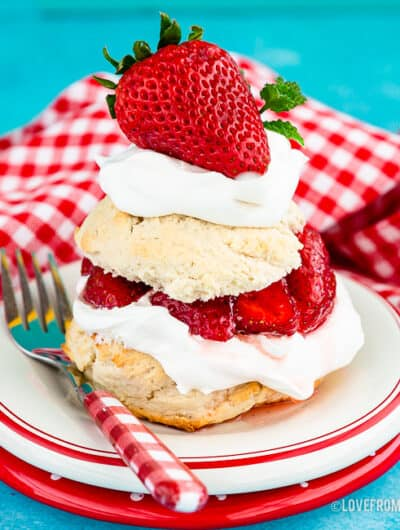 A serving of Bisquick strawberry Shortcake on a white plate with a blue background