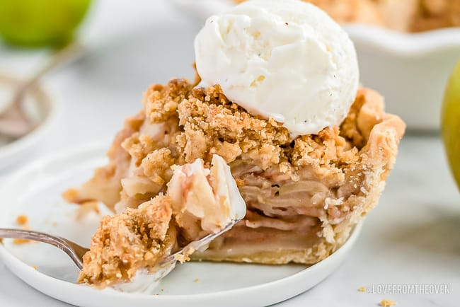 Slice of dutch apple pie with a scoop of vanilla ice cream on top