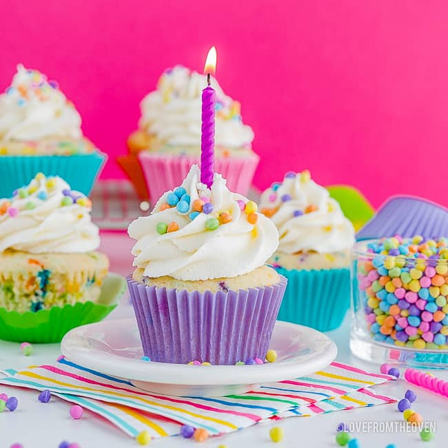 Funfetti cupcakes on a table, one with a lit candle in it
