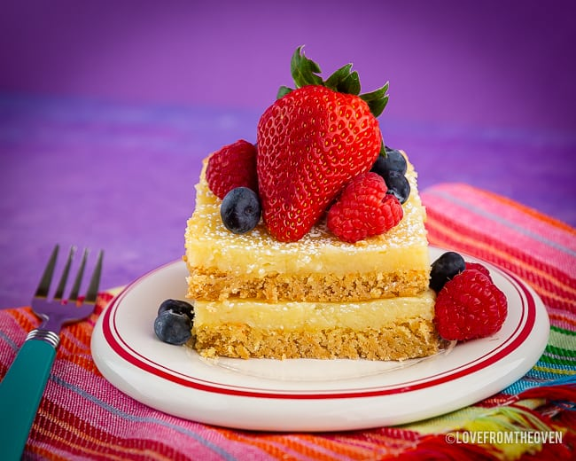 Ooey Gooey Butter Cake on a plate topped with berries