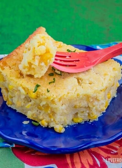Slice of Jiffy Corn Casserole on a blue plate with a red fork