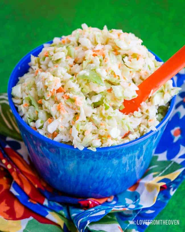 Blue bowl holding KFC Coleslaw Copycat Recipe with a green background
