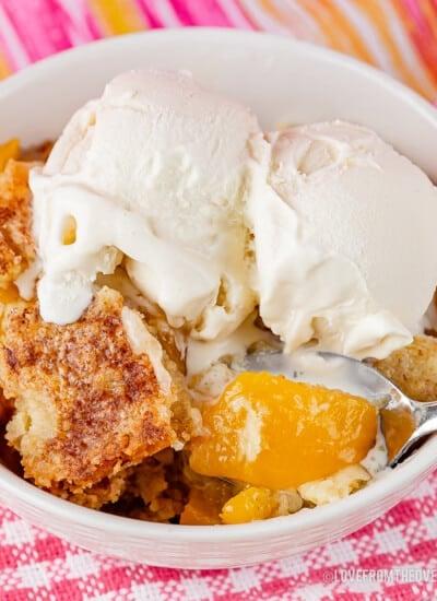 Bowl of peach dump cake topped with vanilla ice cream
