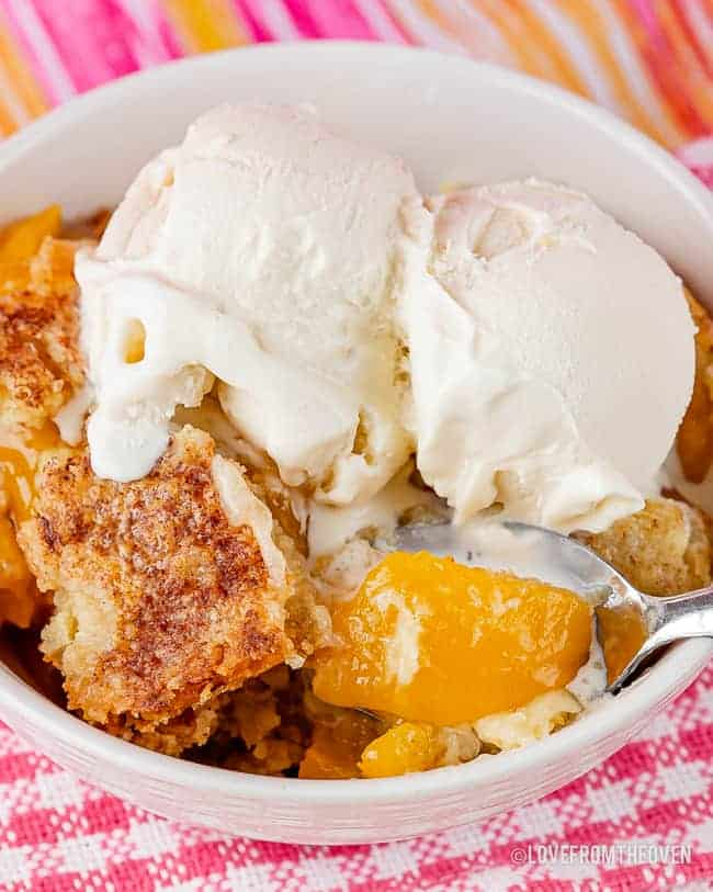 Bowl of peach dump cake topped with vanilla ice cream